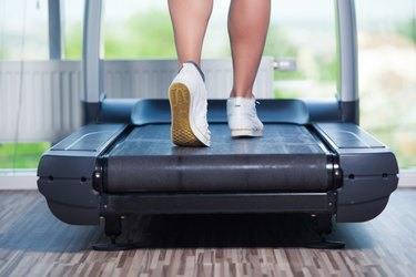 Fitness girl running on treadmill. Woman with muscular legs in