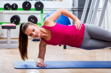 Young, attractive, girl at the gym side planking on the floor in sportswear for better shape, endurance and fitness.