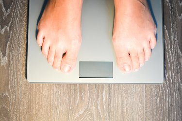 Lose weight concept with person on scale measuring kilograms