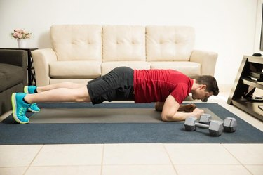 Full length profile view of an athletic man exercising and doing a plank at home