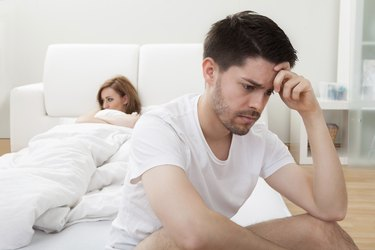 Depressed man sitting on the edge of bed