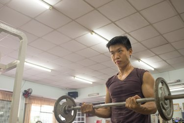 Muscular man exercise with weights in the sport center