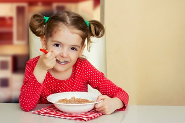 Little girl eating meal.Kid healthy food background.