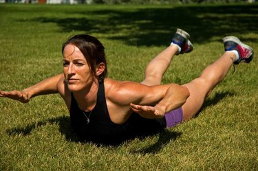 Woman doing a Superman back extension at a park.