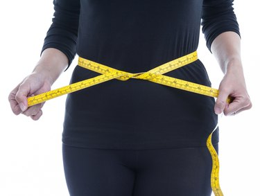 Woman wears black body clothes with yellow measuring tape.