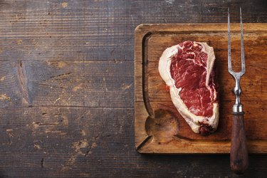 Raw meat Ribeye Steak and meat fork