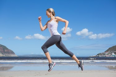 Pretty fit blonde jogging on the beach