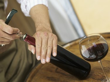 Man opening bottle of wine,close-up of hands