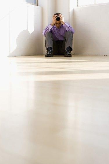 Businessman sitting on floor in corner with head in hands