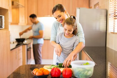 young family preparing meal in kitchen