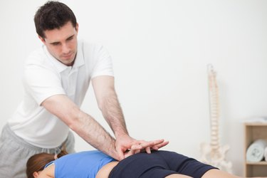 Practitioner pressing the lower back of woman while standing in front of her