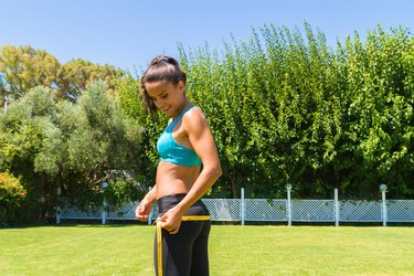 Young brunette sweating athlete in sportswear measuring her hips