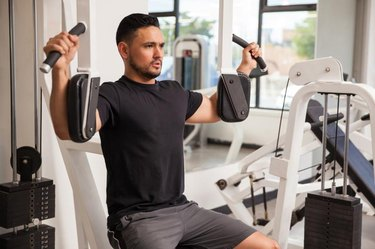 Good looking young man building muscle at the gym using a pec deck machine