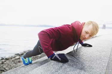 A profile DSLR photo of young male athlete wearing blue running shoes, black tights (pantyhose) and crimson t-shirt with hood. He is doing incline push ups leaning over the stairs of embankment. He is alone in this cold morning. He is looking towards the camera.