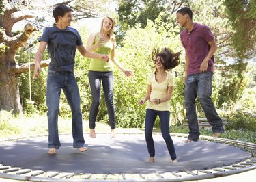 Four Teenage Friends Jumping On Trampoline In Garden
