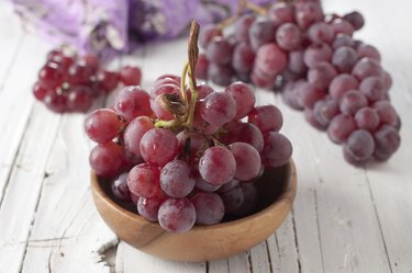 A small bunch of red grapes in a wooden dish