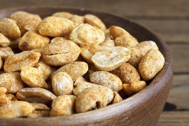 Rustic spicy dry roasted peanuts in rustic wood bowl.