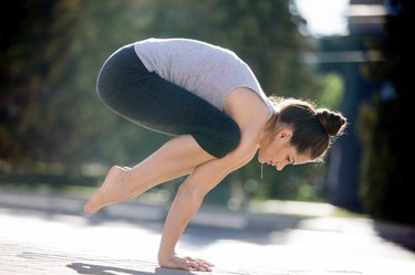 Yoga in the city: beautiful sporty young woman wearing sportswear working out on the street on summer day, doing Crane (Crow) Posture, Bakasana (Kakasana), full length, side view