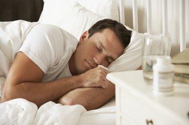 Medication On Bedside Table Of Sleeping Man