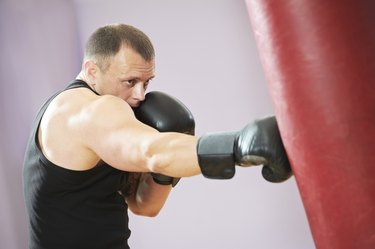 boxer man at boxing training with heavy bag
