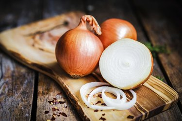 Whole and halved onions on a wooden cutting board.