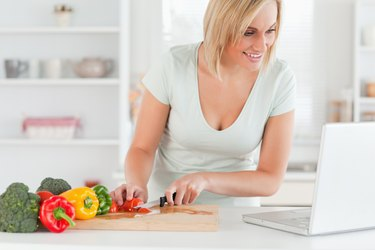 Close up of a woman looking for a recipe on laptop