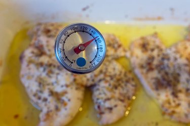 Checking the temperature of baked chicken breasts with meat thermometer