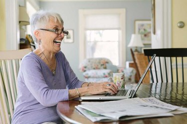 A senior woman working on a laptop at her kitchen table
