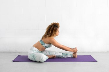 woman does seated hurdler ab exercise on a yoga mat