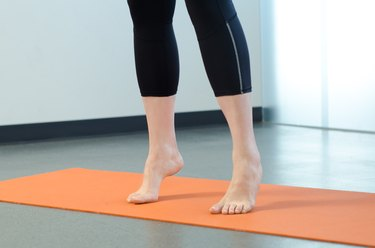 Woman performing standing calf raise for foot pain