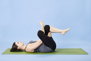 Woman performing Reclining Pigeon pose for back pain