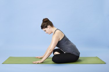 Woman performing full back stretch for back pain
