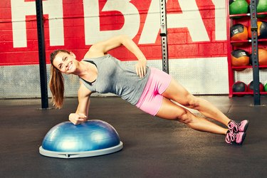 Woman performing side forearm plank BOSU ball exercise