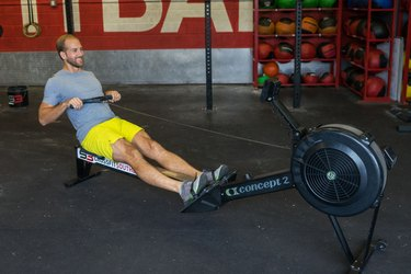 Man using the rowing machine as part of a calorie burning HIIT workout
