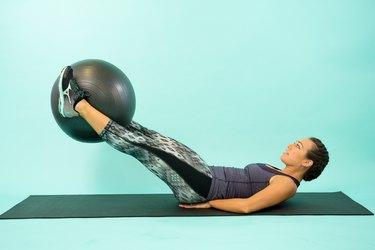Woman performing Swiss ball leg lift.