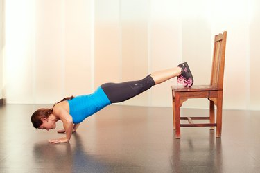 Woman Demonstrating Decline Push-Ups in Her Hotel Room