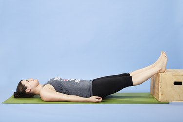 Woman performing assisted leg raise for back pain