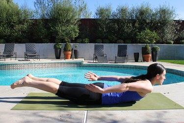 woman doing locust yoga pose