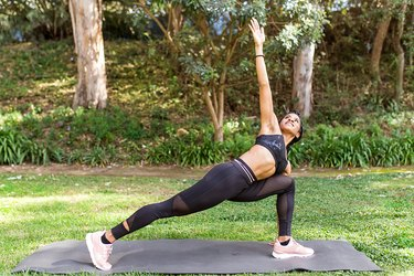 woman doing lunge and twist on a yoga mat outside