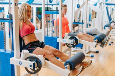 three young friends working out in gym. saturated training of man and two women. Good results. Different exercises