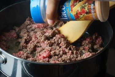 adding seasoning to beef in pot