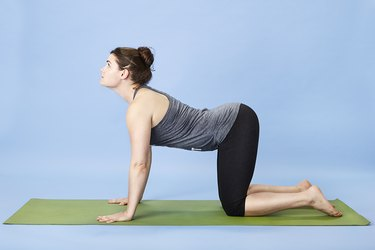 Woman performing cat-cow pose for back pain