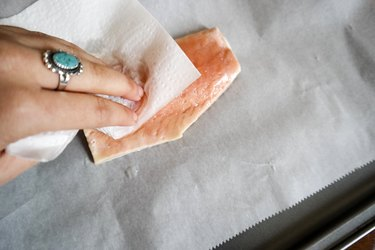 Woman preparing a salmon filet to grill in the oven