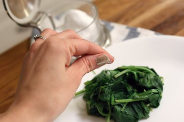 hand sprinkling steamed spinach on white plate with salt and pepper