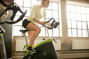 woman riding stationary bike in gym