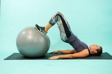 Woman performing Swiss ball hamstring curl.