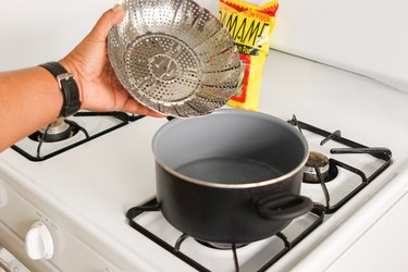 Metal steamer basket being put into a saucepan on the stove.