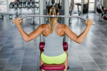 Woman doing behind the neck lat pulldown at the gym