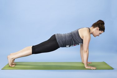Woman performing plank pose for back pain