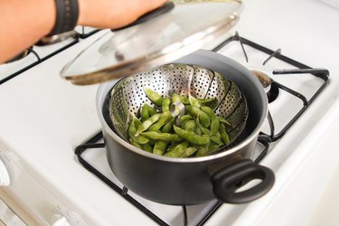 Frozen edamame in a steamer basket and saucepan on the stove.